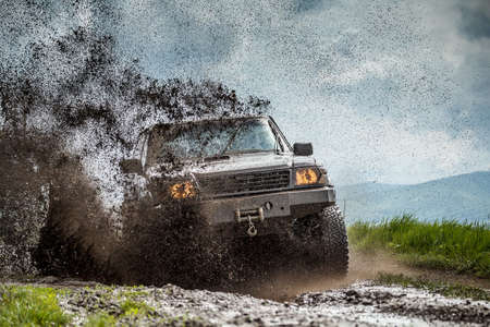Off road car sprays mud Stock Photo