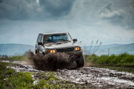 off road vehicle: Big four by four off road car crossing puddly road Stock Photo