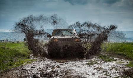 Внедорожные автомобиль в грязной дороге Фото со стока