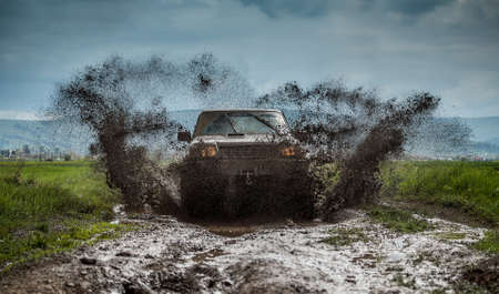 Off road car in muddy road Imagens