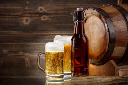 Beer glasses with a wooden barrel. photo