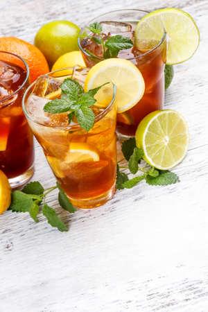 té helado: Vasos de té helado con cubitos de hielo en mesa de madera