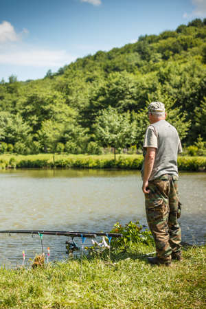 Fisherman with fishing rod standing on lakeside photo