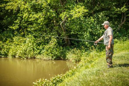 Mature fisherman on the lake photo