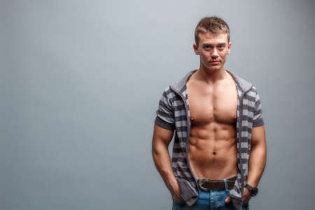 Muscular young man on gray background photo