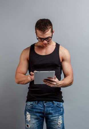 Young man using digital tablet on gray background photo