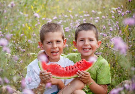 Two children eating watermelon outdoors in meadow photo