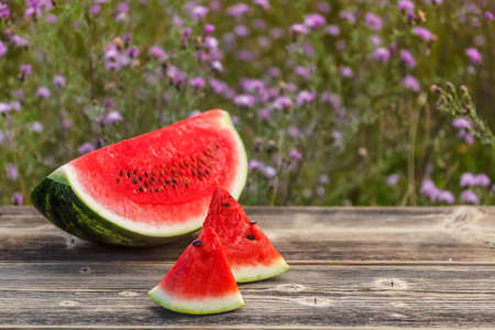 Big slice of juicy watermelon on rustic wooden table photo