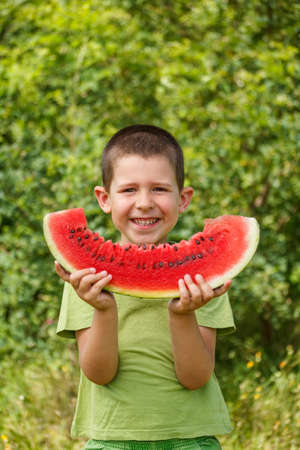 Happy child with big red slice of watermelon  photo