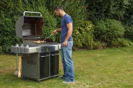 Young man at a barbecue grill Stock Photo