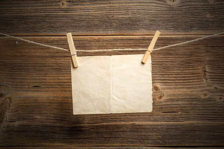 attach: Paper attach to rope with clothes pins on wooden background
