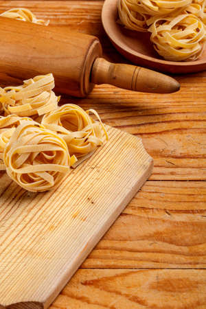 rollingpin: Tagliatelle and rolling-pin on wooden board