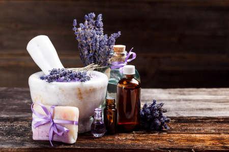 Still life with lavender salt, bottles, soap and dry lavender flower, on wooden table