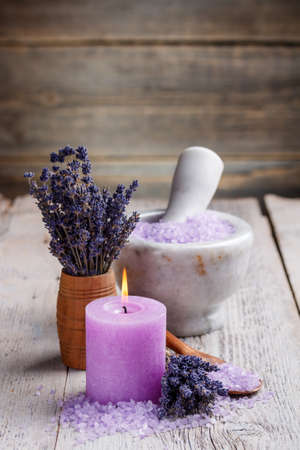 perfumed candle: Dried lavender in wooden bowl, bath salts andcandle.
