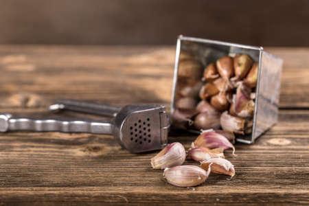 garlic clove: Garlic press  and garlic clove on wooden table