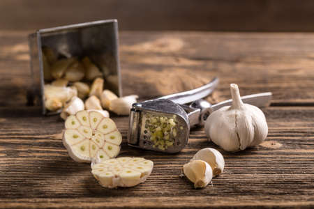 Garlic and garlic press on rustic wooden board Stock Photo
