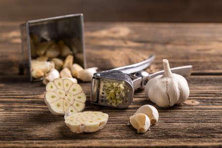 Garlic and garlic press on rustic wooden board Standard-Bild