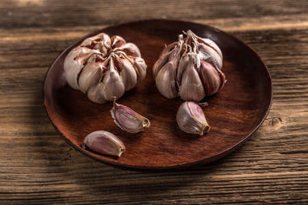 Bulb of garlic in wooden plate photo
