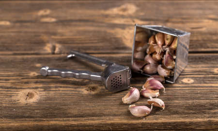garlic clove: Garlic clove and press on rustic board