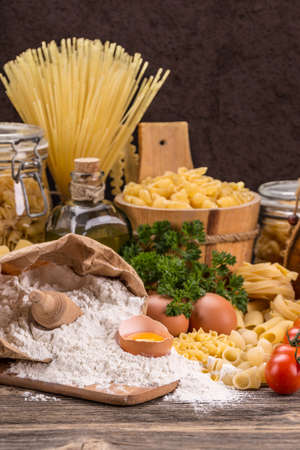cooking oil: Raw food composition with pasta, flour and egg Stock Photo
