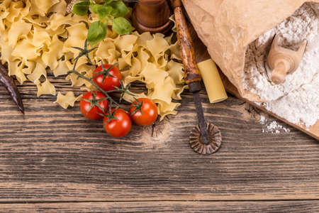 Pasta products on rustic wooden board photo