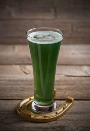 alehouse: Glass of green beer and horseshoe for St Patricks day Stock Photo