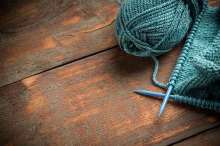 woollen: Woollen thread and knitting needle on wooden background