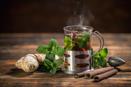 taza de t�: Taza de t� de hierbas con menta fresca en mesa de madera Foto de archivo