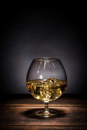 cognac: Cognac in goblet on wooden table