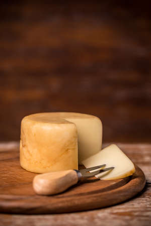 chopping board: Cheese on a chopping board with fork