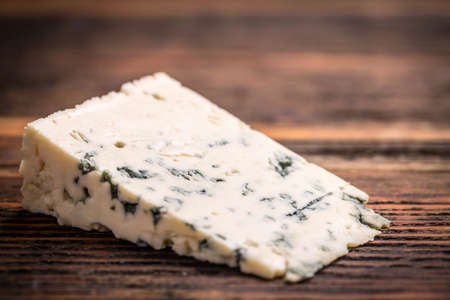 veining: Piece of gorgonzola cheese on wooden board Stock Photo