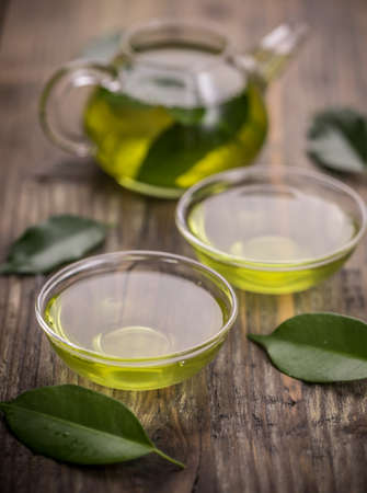 herb tea: Cup with green tea and green leaves Stock Photo