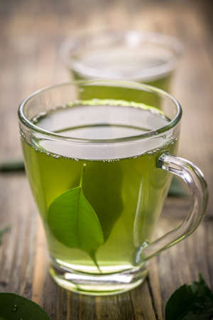 plant antioxidants: Cup with green tea and green leaves Stock Photo
