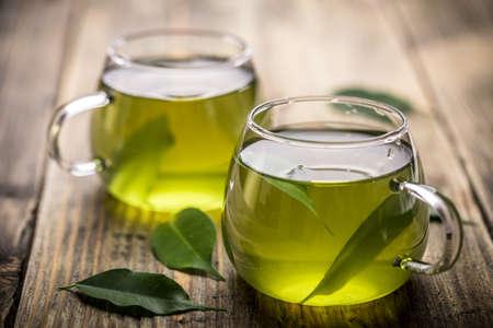 Thé vert avec des feuilles de thé dans l'eau Banque d'images