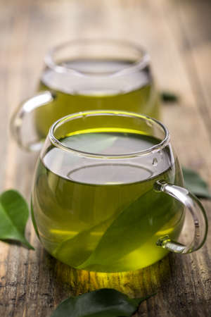sencha tea: Green tea in glass cup on vintage wooden background