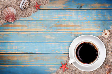 starfish beach: White cup with coffee on blue wooden background