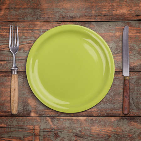 vintage cutlery: Green empty plate and wooden vintage cutlery on vintage wooden background