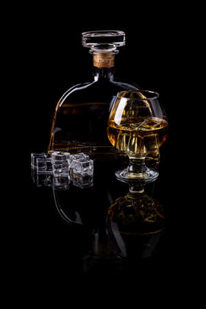 hard liquor: A glass and a bottle of hard liquor against black background