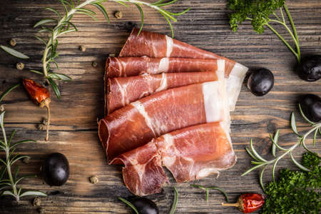 Sliced prosciutto on a vintage wooden background Stock Photo