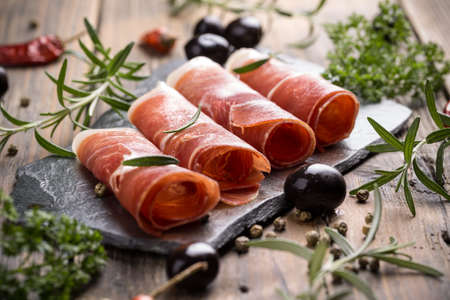 Sliced prosciutto with herbs and olive