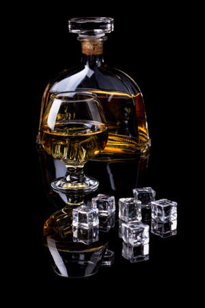 hard liquor: A glass and a bottle of hard liquor whit ice cub against black background