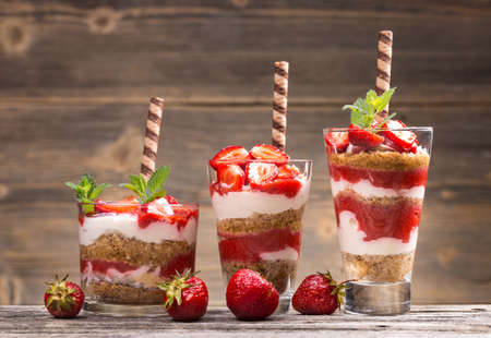 Fresh strawberry yogurt parfait on wooden background Archivio Fotografico