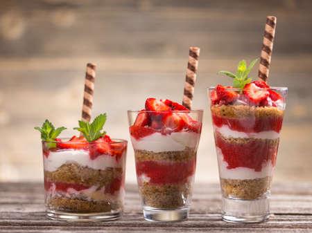 Dessert with fresh strawberries on wooden background
