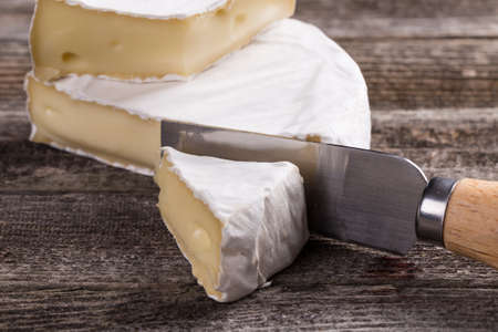 cheese knife: Camembert cheese on a wooden rustic table Stock Photo