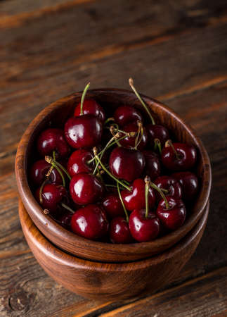 sour cherry: Sour cherry in bowl on wooden background Stock Photo