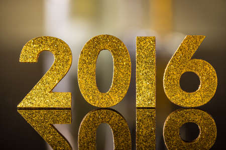 golden background: 2016 year golden number on reflection surface Stock Photo