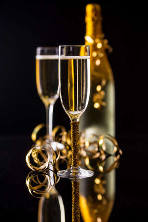 Champagne bottle and champagne glass in holiday setting