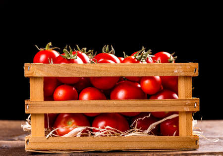 wooden crate: Fresh tomatoes on the vine in a wooden crate