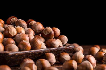 cobnut: Hazelnuts in bamboo plate old black background Stock Photo