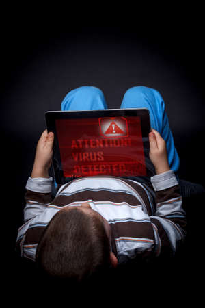 hacked: Kid holding the tablet with virus Stock Photo